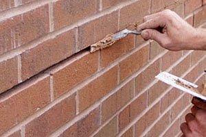 Zummo Meat Brick Wall Restoration, man puts brick clay in between bricks.